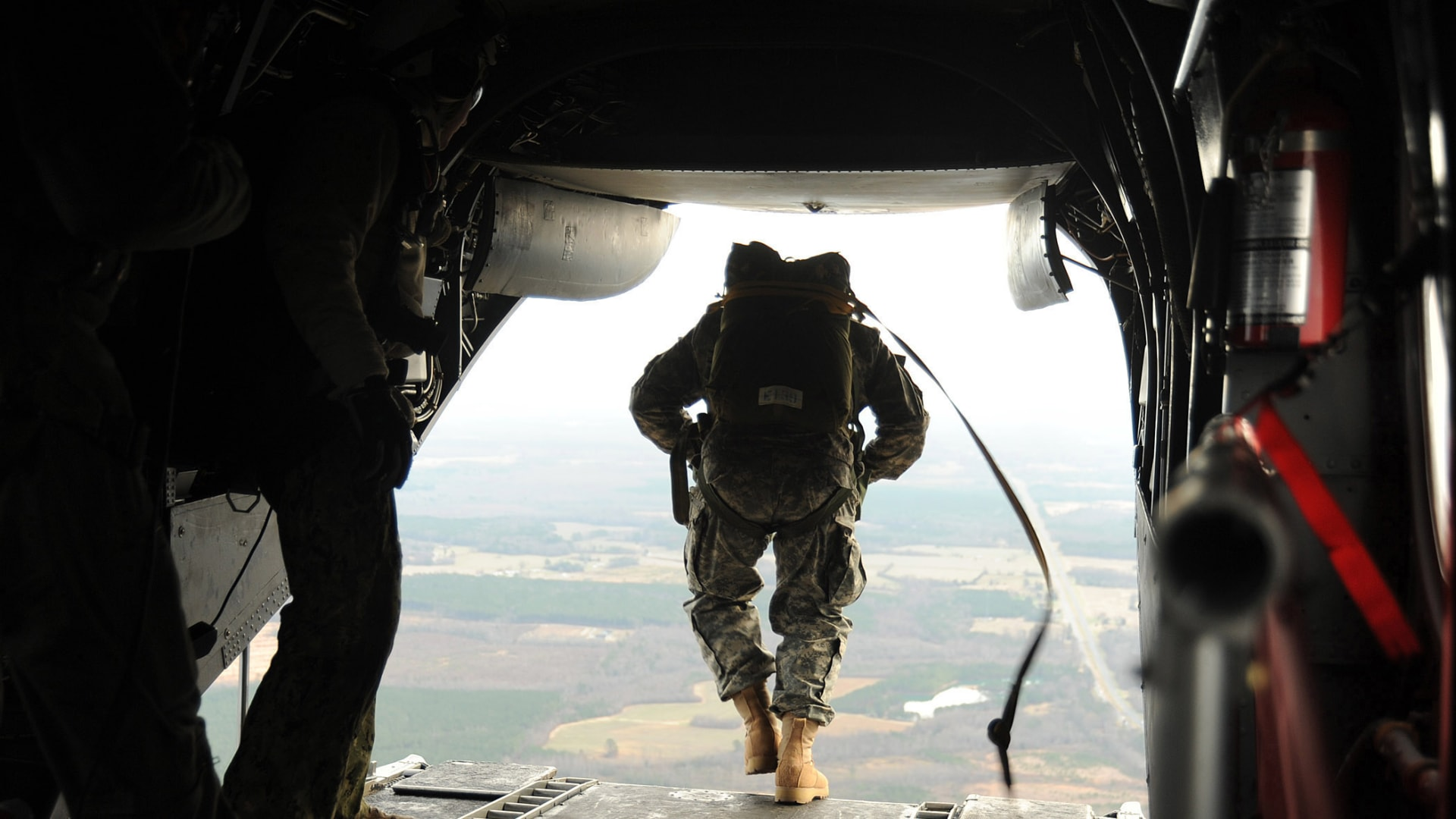 Navy SEALs jump from a CH-46E Sea Knight helicopter during training near Fort Pickett.