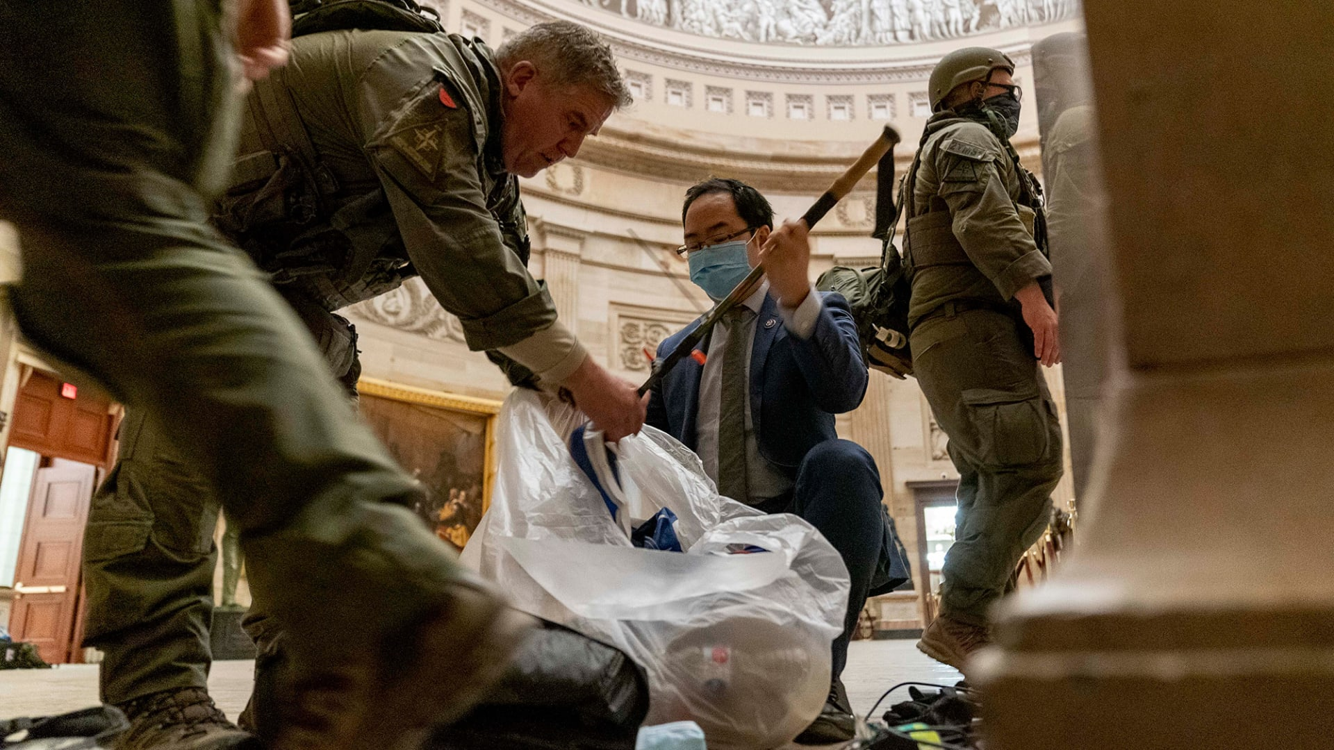 Representative Andy Kim helps ATF police officers clean up debris and personal belongings strewn across the floor of the Capitol Rotunda in the early morning hours of Thursday, January 7, 2021, after a rioting mob stormed the Capitol on Wednesday.
