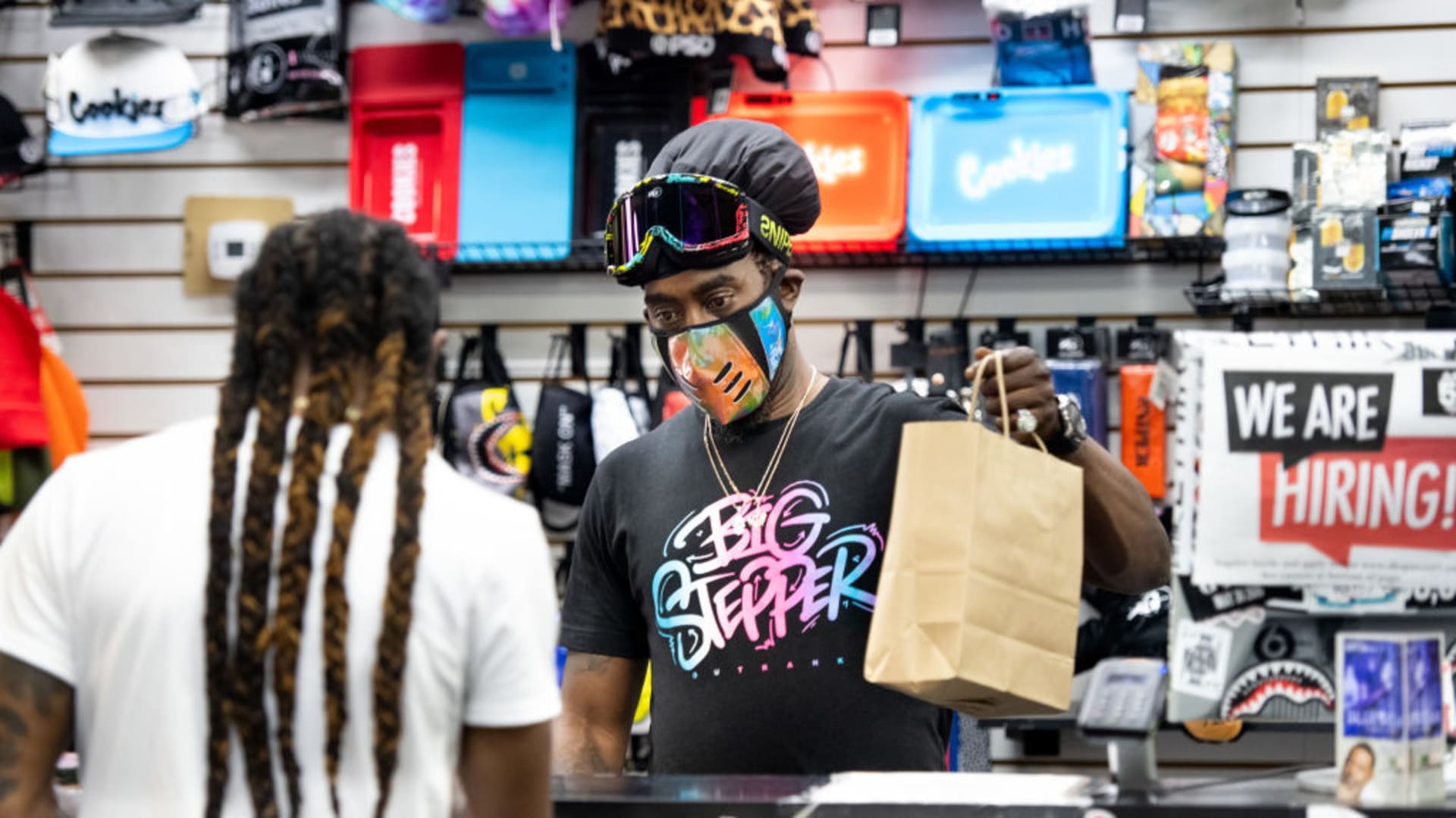 Small-business owner Birl Hicks helps a customer at Area 57 at Columbia Place Mall in Columbia, South Carolina.