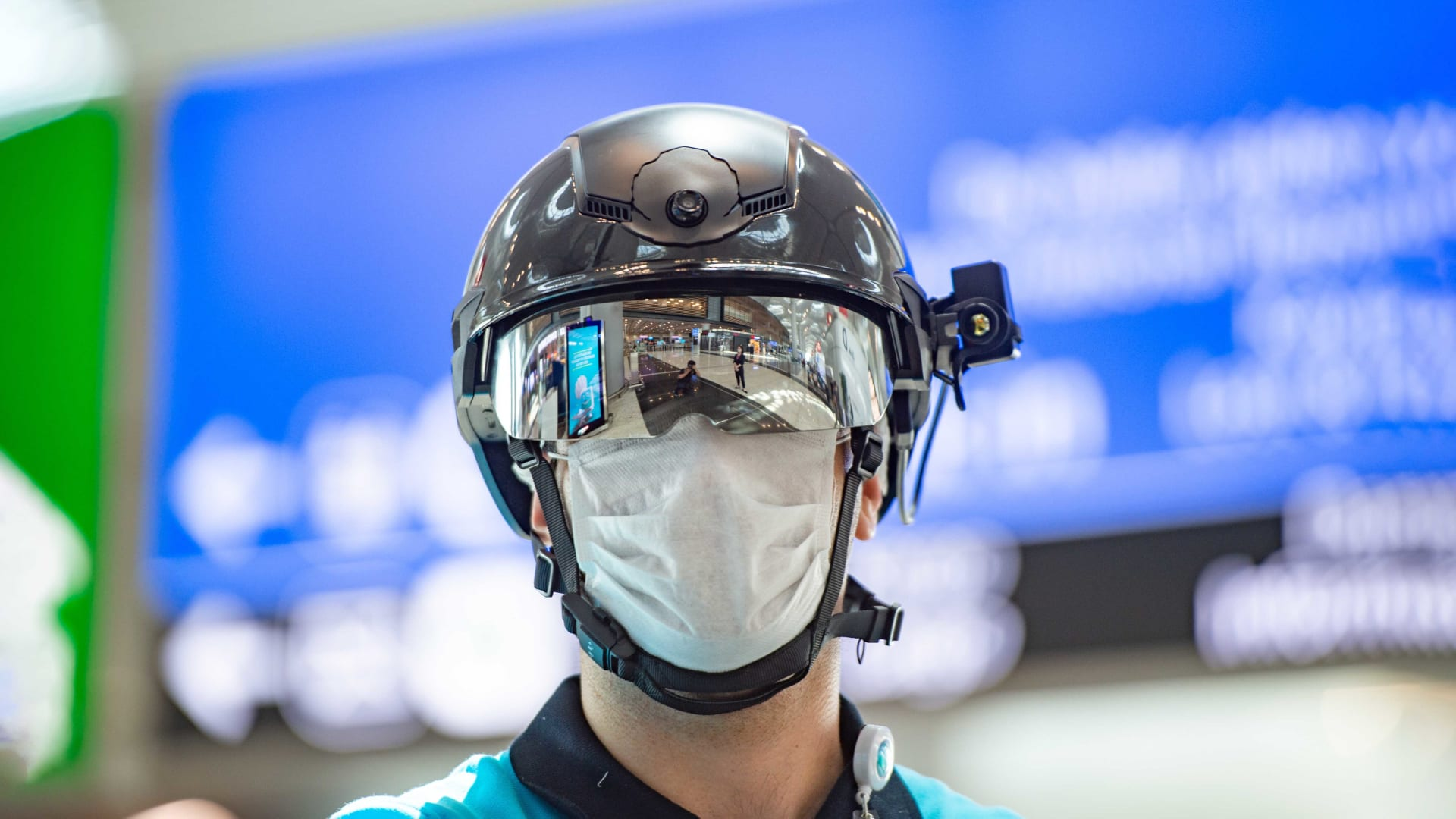 An employee wearing a thermal imaging VF helmet monitors people at Turkey's Istanbul Airport.