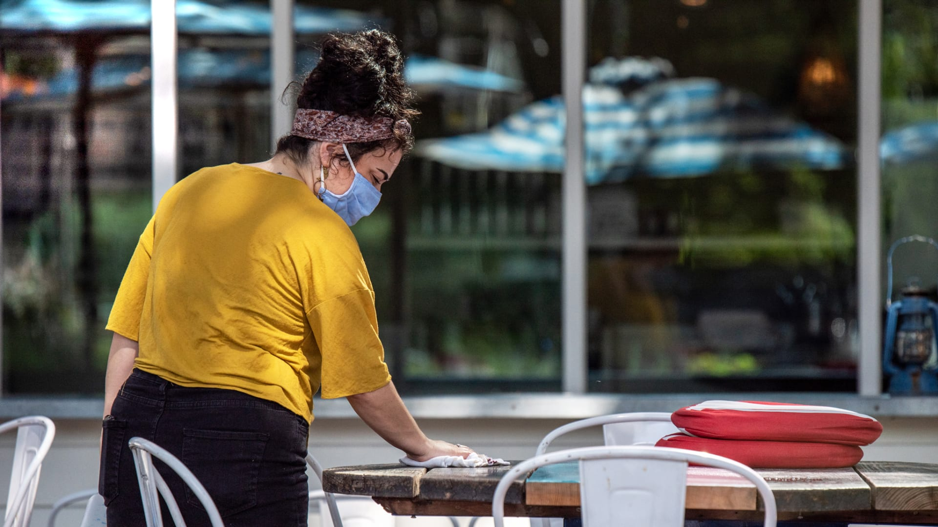 A restaurant worker cleans a table before opening in Austin on Thursday, June 25, 2020.