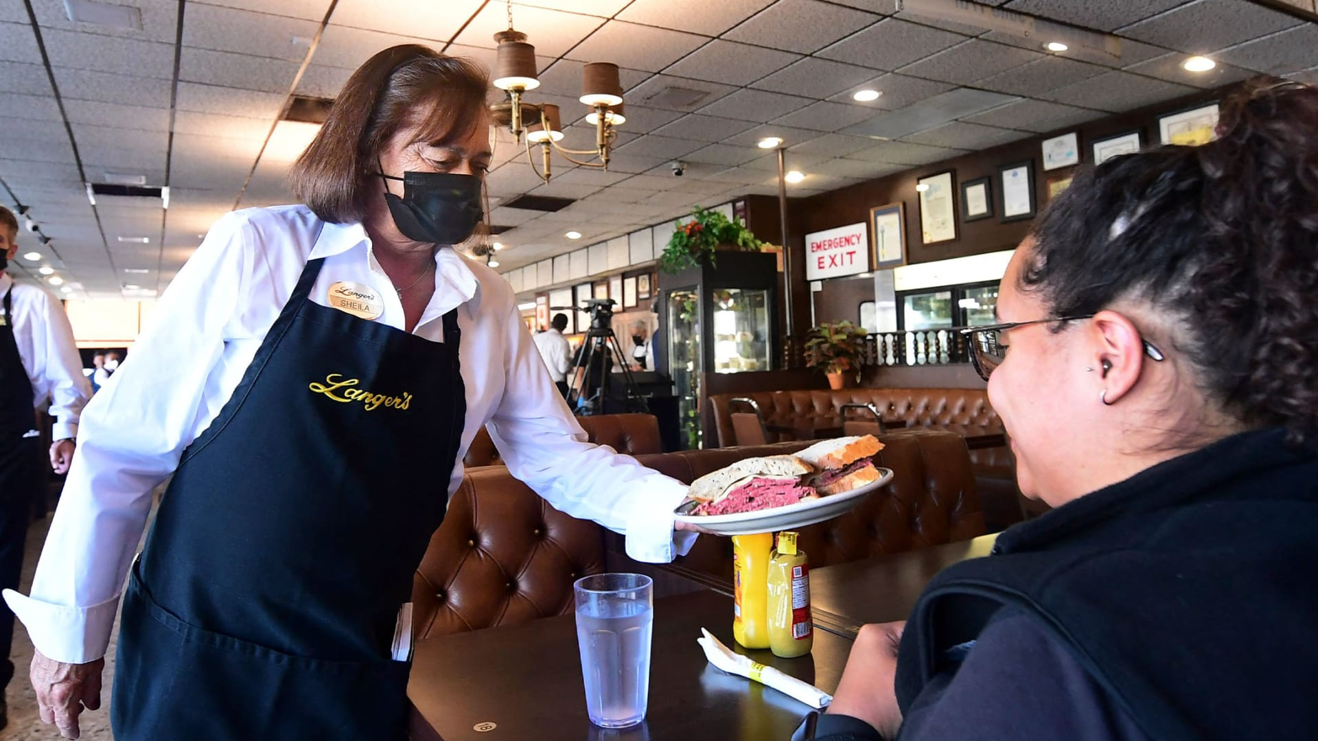 Waitress and twenty-year employee Sheila Abramson serves a sandwich to a customer at the reopening of Langer's Delicatessen-Restaurant in Los Angeles on June 15, 2021.