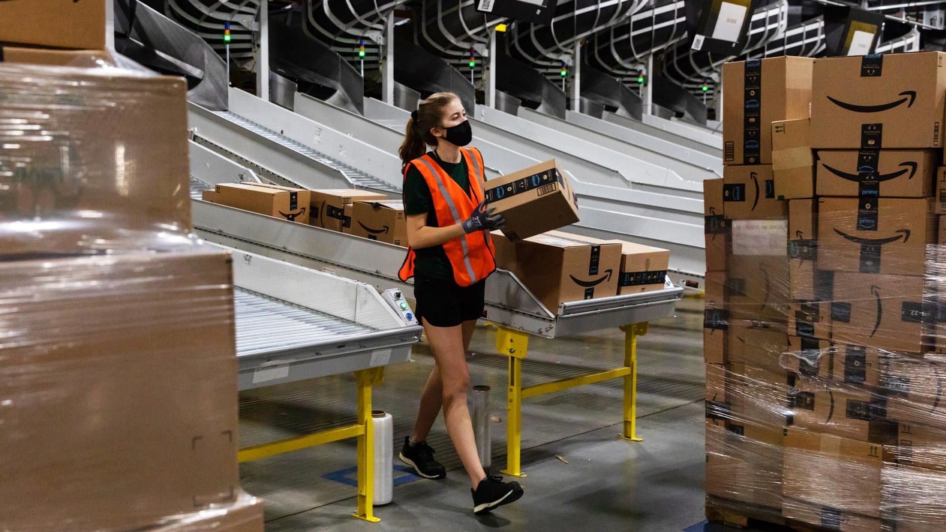 A worker loads boxes onto a pallet at an Amazon fulfillment center in Raleigh, North Carolina, during Prime Day 2021.