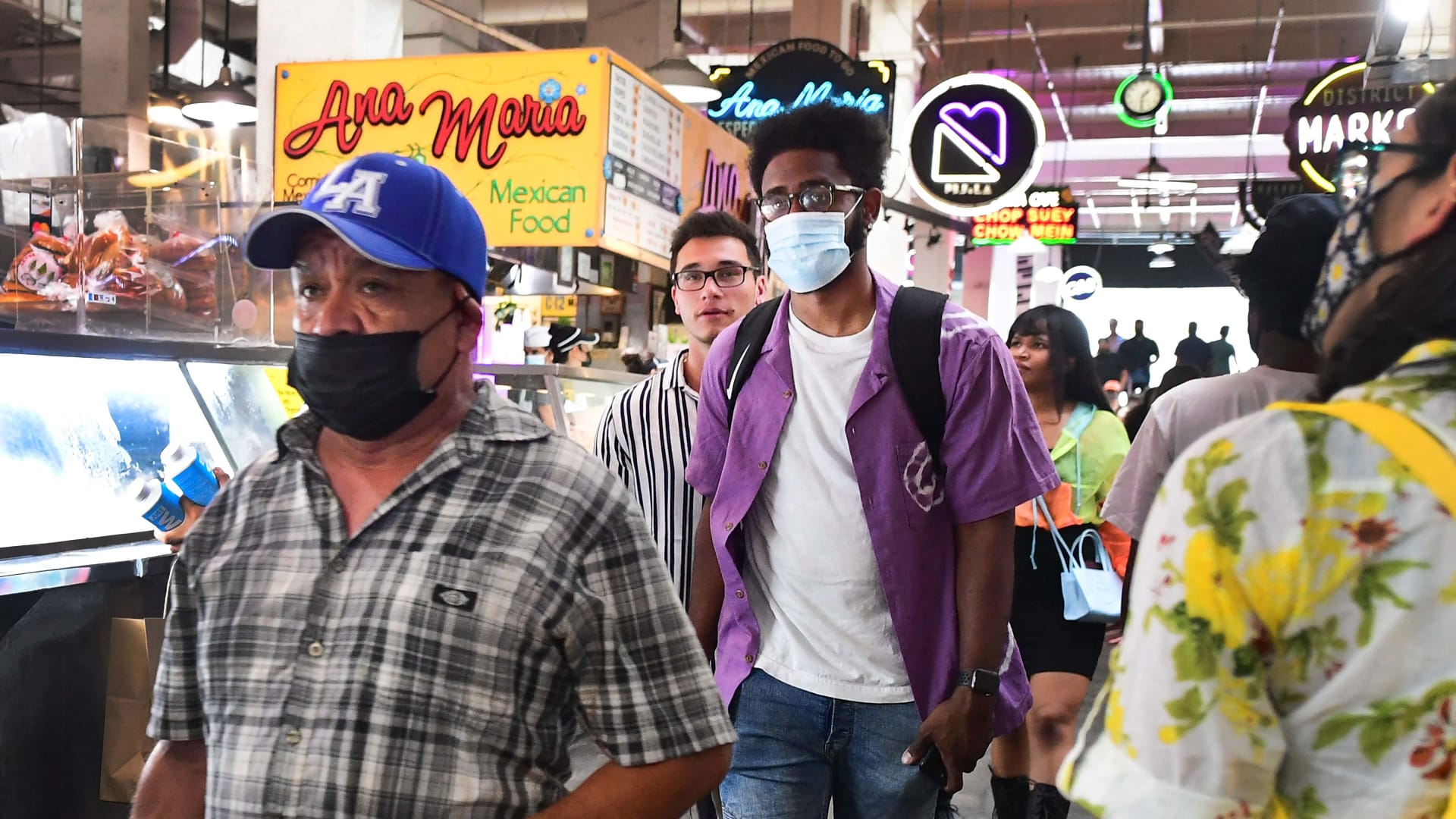 Masked and unmasked people make their way through Grand Central Market in Los Angeles on June 29.