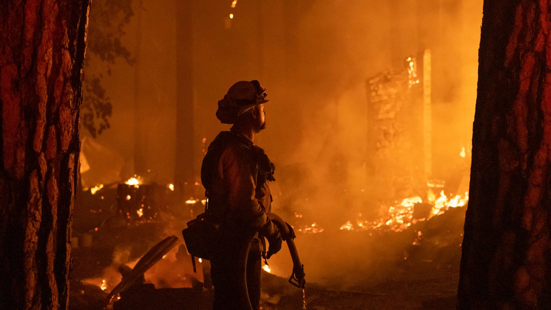 A firefighter monitors a fire as multiple structures burn in the Indian Falls neighborhood during the Dixie Fire near Crescent Mills, California.