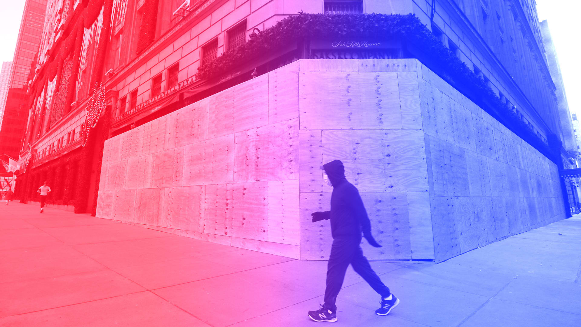 A person walks past a boarded-up entrance and windows of the Saks Fifth Avenue store on Fifth Avenue ahead of expected election day protests on October 31, 2020 in New York City.
