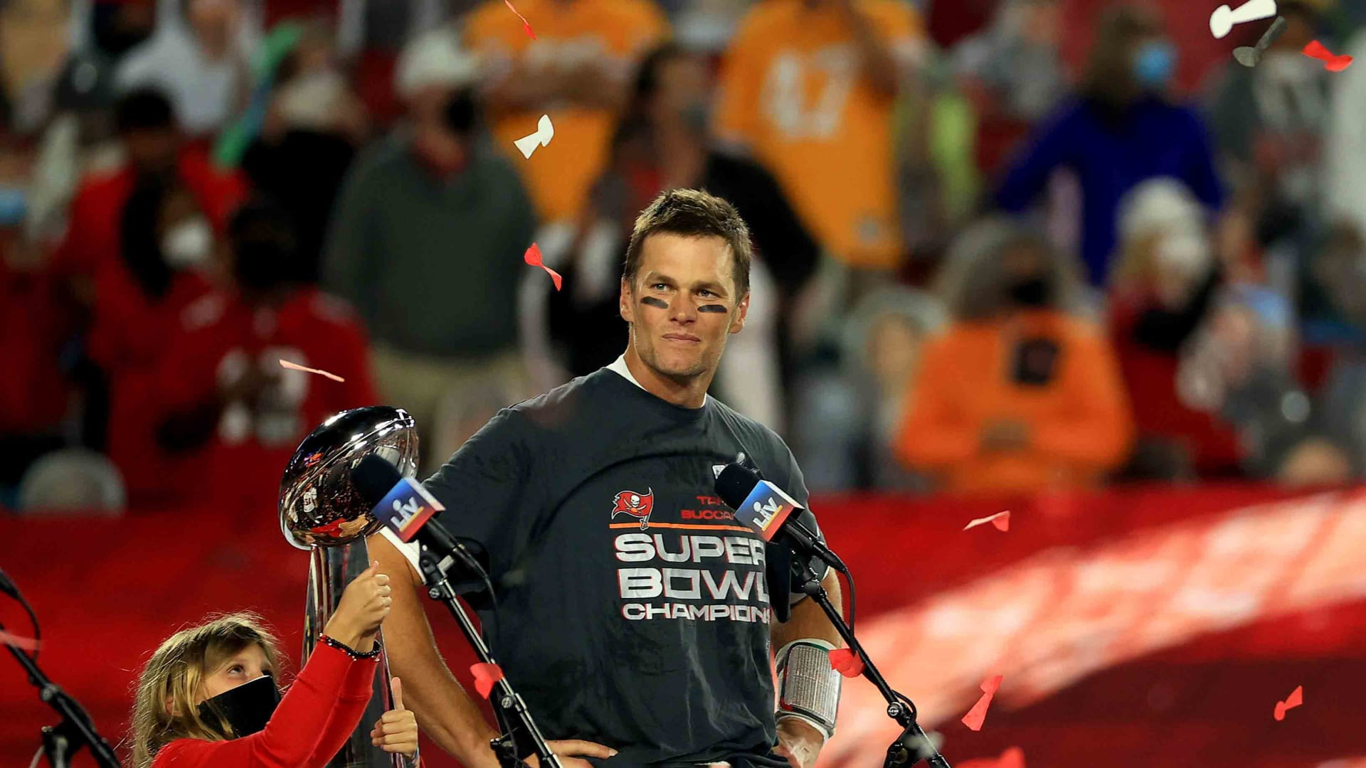 Tom Brady celebrates the Tampa Bay Buccaneers win over the Kansas City Chiefs in Super Bowl LV, as his daughter Vivian holds the Lombardi Trophy.
