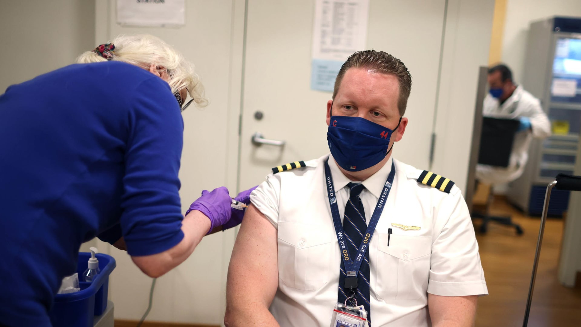 United Airlines pilot  receives a COVID-19 vaccine from at United's onsite clinic at O'Hare International Airport.