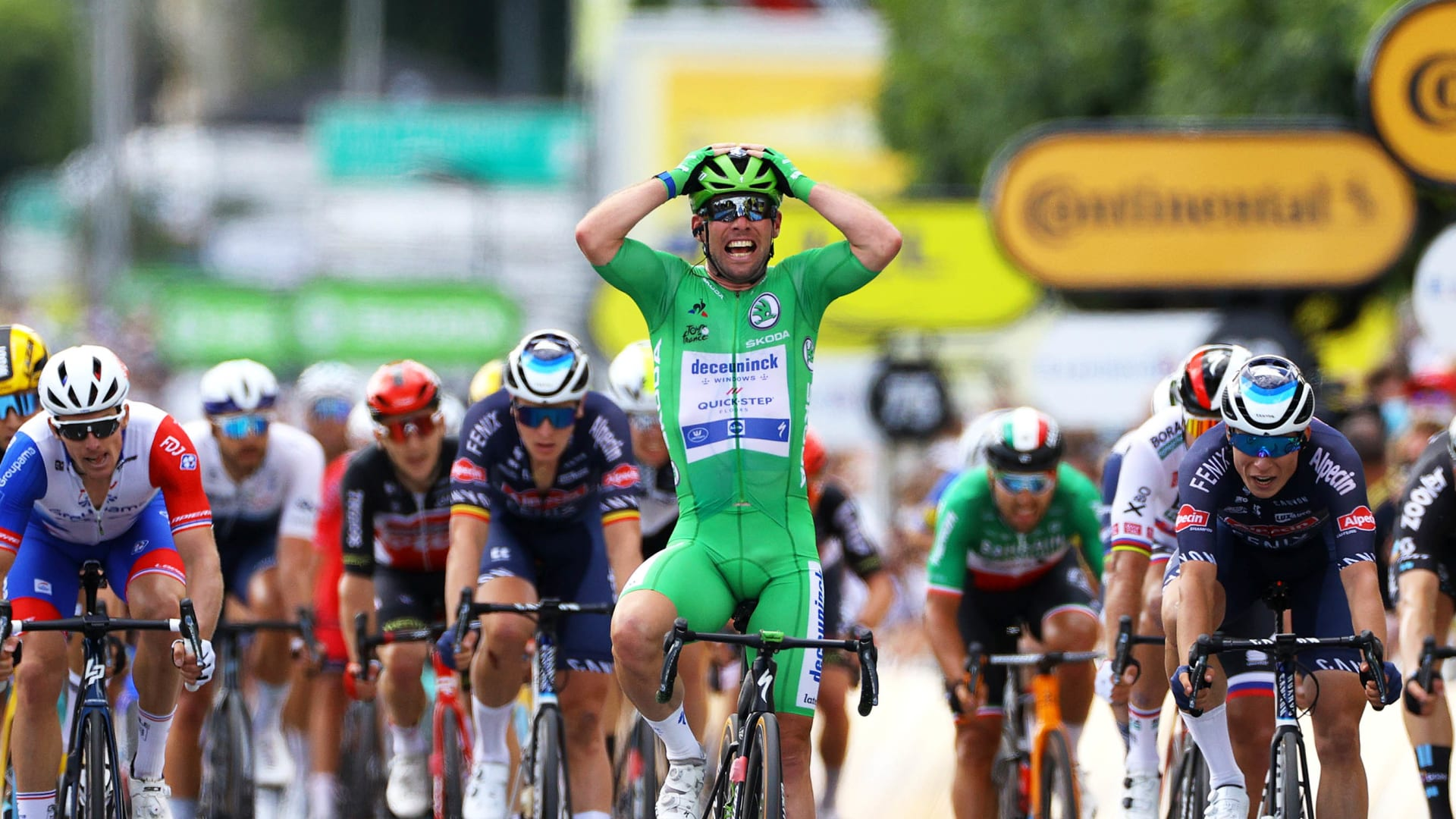 Mark Cavendish celebrates while crossing the finish line of the sixth stage of the Tour de France.