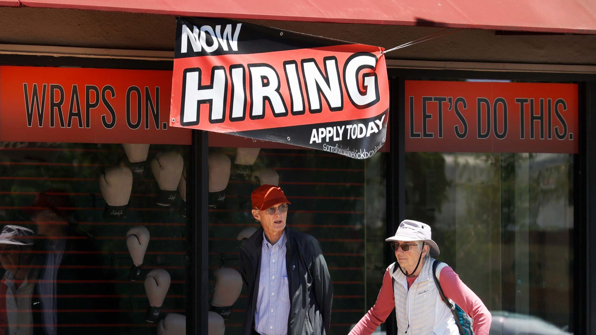 """Pedestrians walk by a """"Now Hiring"""" sign in front of a boxing gym on July 07, 2021 in San Rafael, California."""