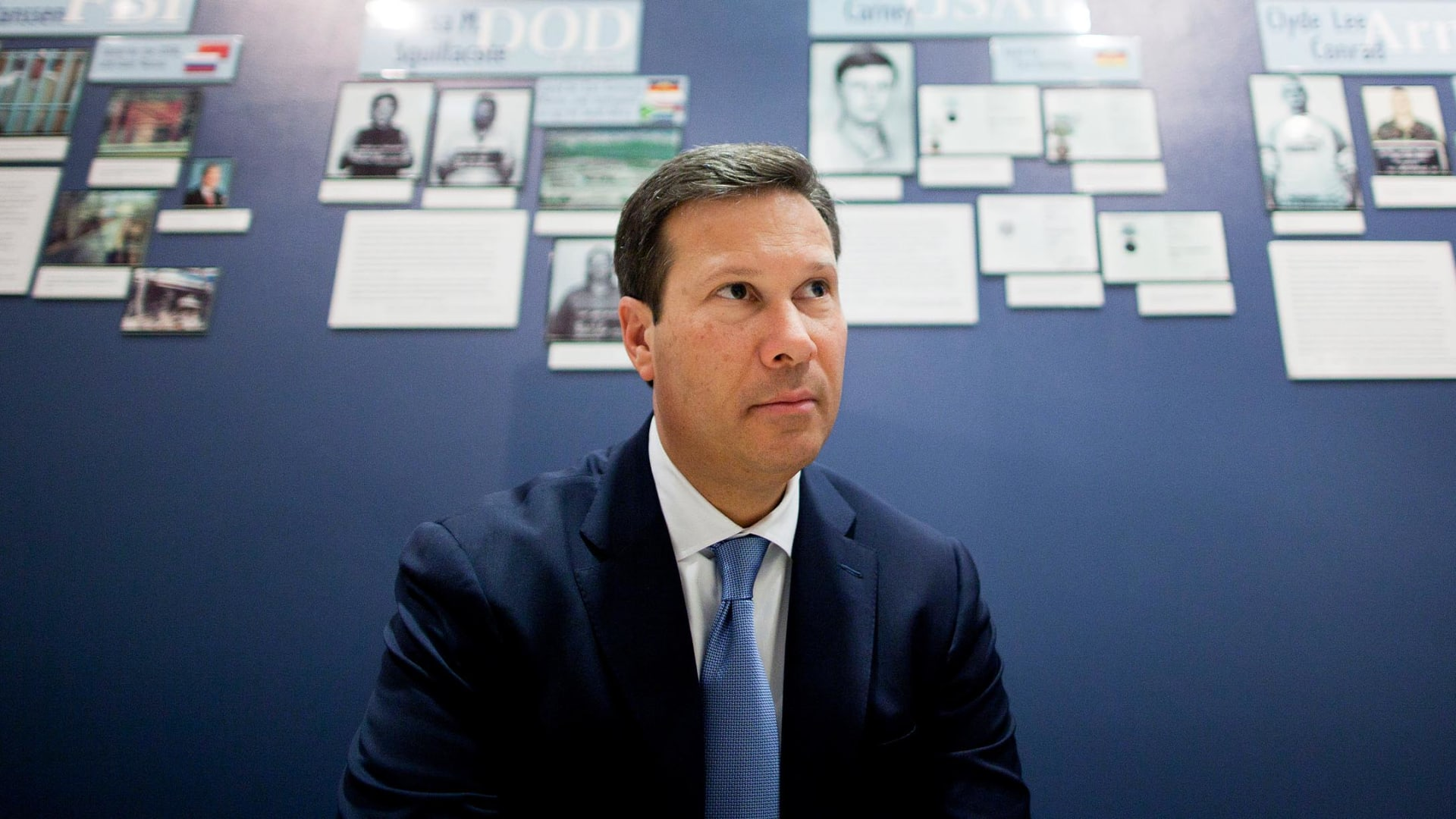 Frank Figliuzzi sits in front of a wall of convicted spy profiles at FBI headquarters in Washington, D.C.