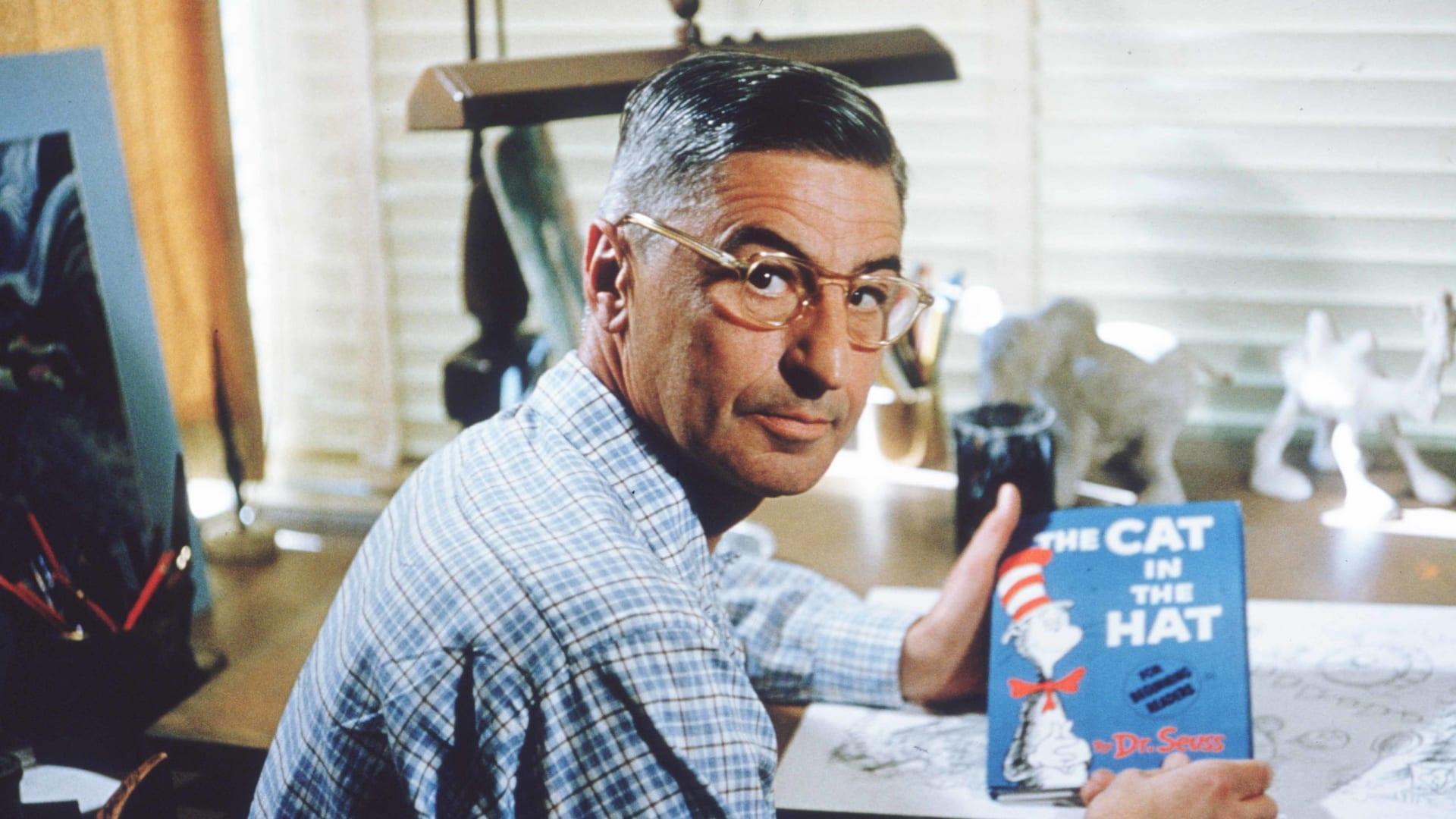 The late American author and illustrator Theodor Seuss Geisel (a.k.a. Dr. Seuss) at his drafting table in his La Jolla, California, home office in 1957.