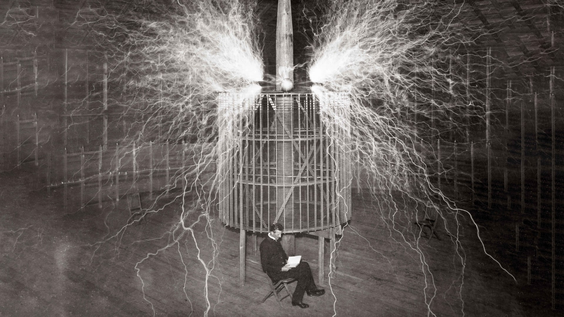 "Nikola Tesla, Serbian-American physicist sitting in his Colorado Springs laboratory with his ""Magnifying transmitter"""