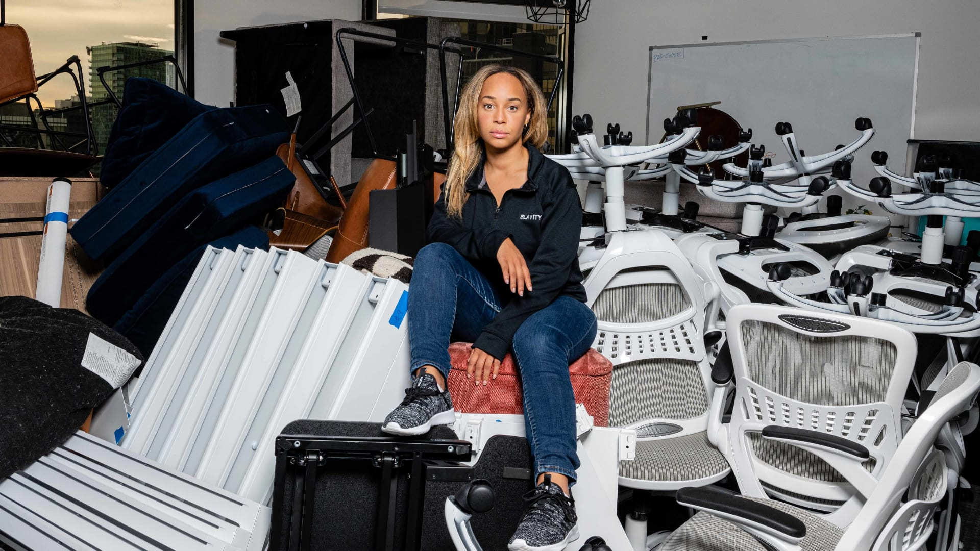Morgan DeBaun, founder and CEO of Blavity, sits atop a pile of no-longer-in-use furniture in her L.A. office.