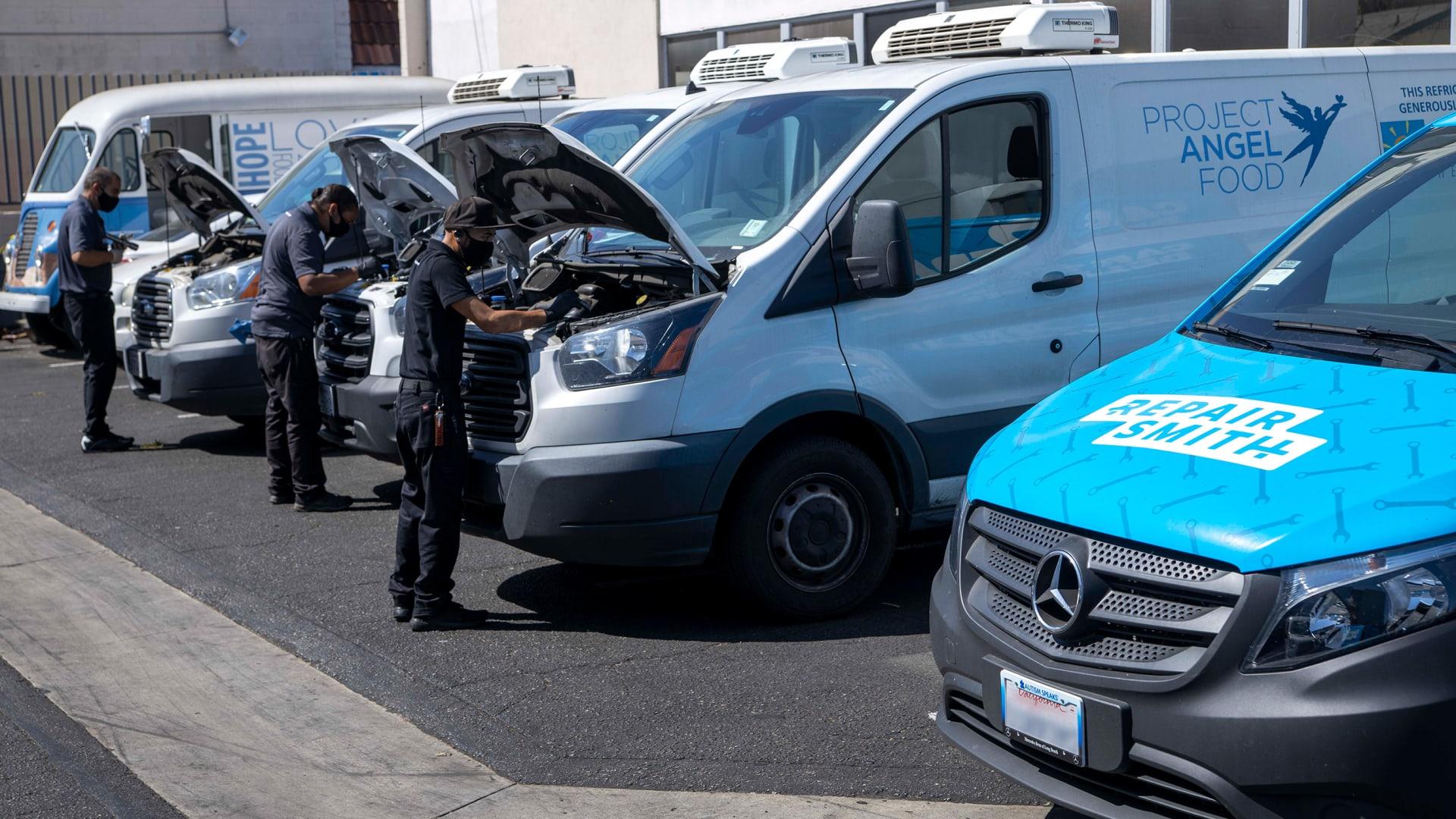 Repair Smith mechanics perform free tune-ups on Project Angel Food's fleet of vans.