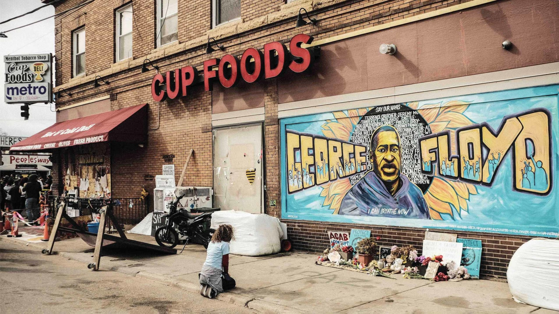 A woman pays respect to a mural of George Floyd where he was killed by police in Minneapolis.